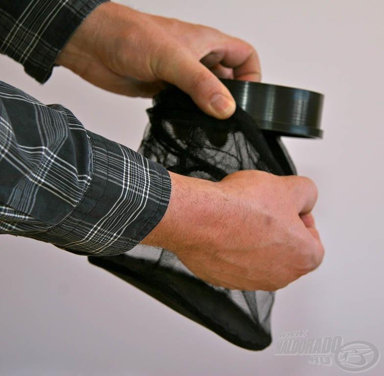 Elsőként a csapda aljára belülről kell rögzíteni a hálós tartályt a gumírozott pánt segítségével